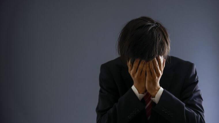 悩み過ぎて頭を抱える男性